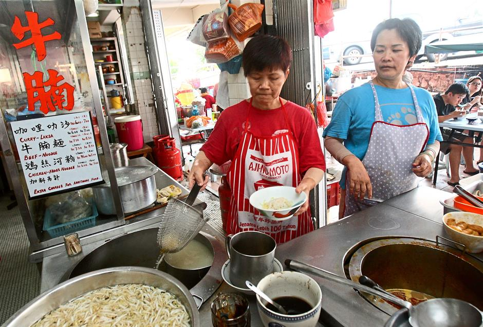 Old-timers: Ah Moi (left) and Kam Chee have been selling their famous curry laksa in Sea Park, PJ for over 20 years.