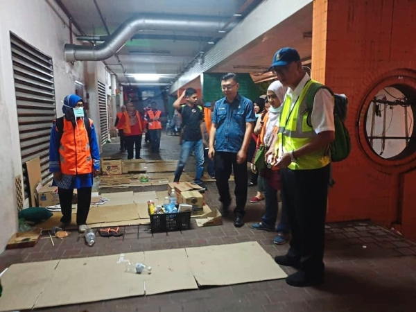 Phee (in reflective vest) and Komtar assemblyman Teh Lai Heng (in blue shirt) looking at the cardboard sheets used by the vagrants.
