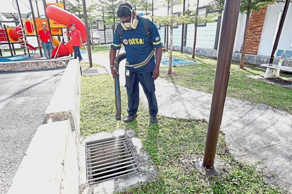 A field worker spraying a thin film of oil and chemical into the drains filled with stagnant water within the compound of Damai Apartments. — Photos: FAIHAN GHANI/The Star