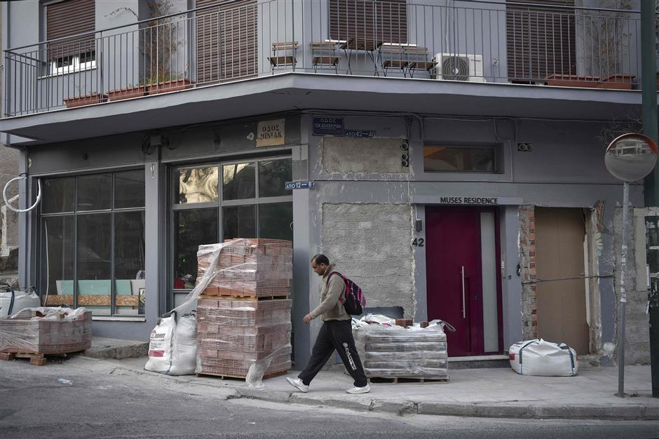 A man walks past a building under consutruction, in Athens, on March 19, 2019. - The Greek chamber of hotels commissioned a Grant Thornton study that found that over 76,000 properties in Greece are available on home-sharing platforms. The study argued that declining availability had pushed up rents in central Athens by 9.3 percent in a year, disproportionately affecting poorer sections such as pensioners and single-parent families. (Photo by LOUISA GOULIAMAKI / AFP)