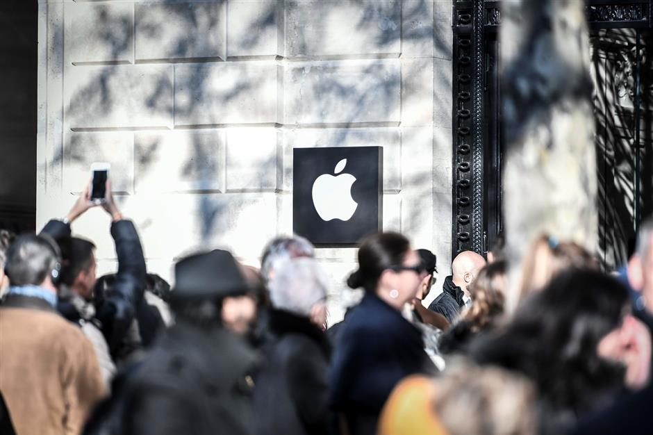 People queue outside the new Apple store on its opening day on the Champs Elysees Avenue in Paris on November 18, 2017. (Photo by STEPHANE DE SAKUTIN / AFP)