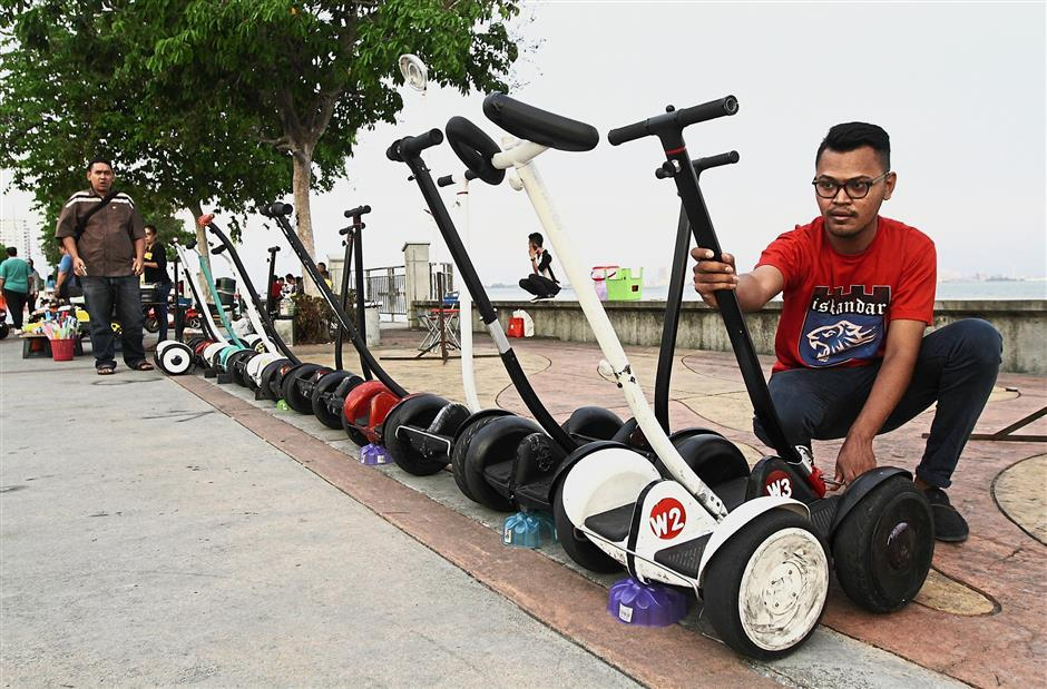 Mohd Nasrudin arranging the Ninebot scooters that he rents out for recreational purpose after obtaining a permit.