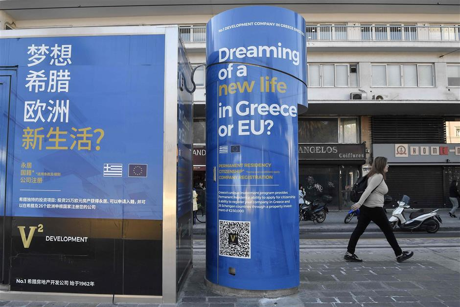 A woman walks past advertisement about property sold for a Golden Visas in the Syntagma square, in Athens, on March 6, 2019. - According to Airbnb data, there are over 8,000 apartments for rent in central Athens alone, at an average of 67 euros per night, including some 1,200 flats in districts close to the Acropolis. About half are multi-listings by owners with more than one property online, Airbnb says. Among them are a few hundred foreigners -- mainly Chinese, Russians and Israelis -- who tapped into a golden visa programme introduced in 2013 for property purchases over 250,000 euros ($285,000), says Lefteris Potamianos, head of the Athens real estate association. (Photo by LOUISA GOULIAMAKI / AFP)