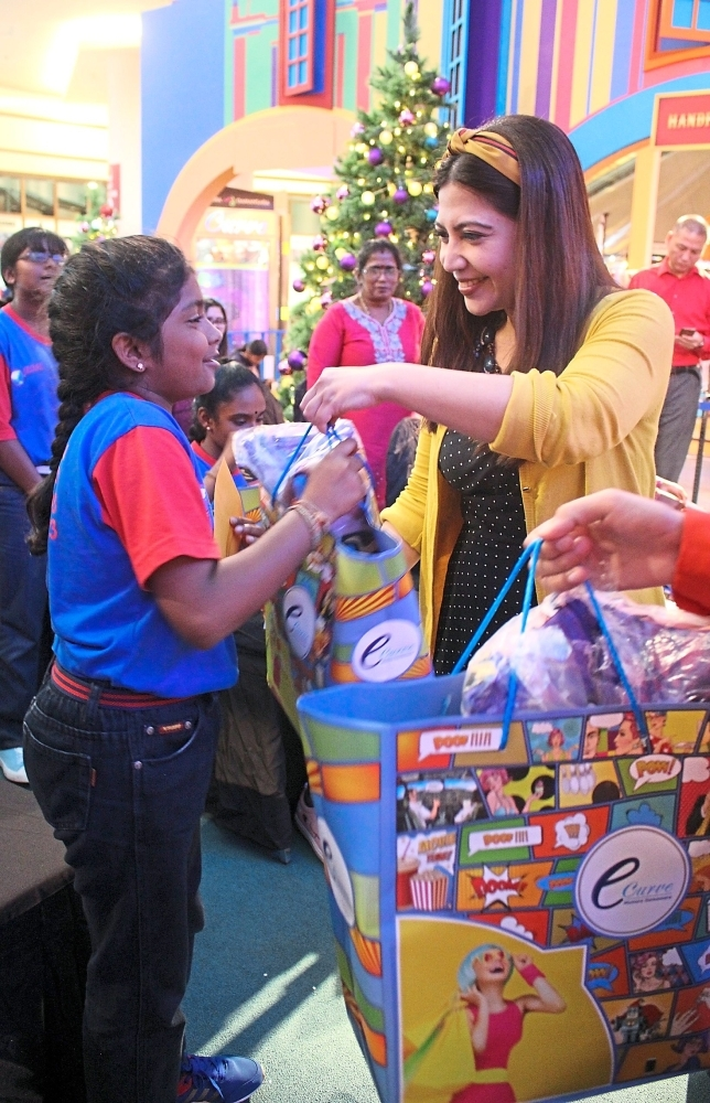 Gina (right) giving out gifts to the children at the Christmas campaign at The Curve.