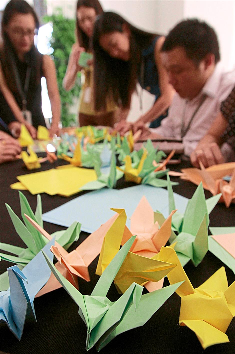 Participants of the event at Gurney Paragon Mall folding their paper cranes inscribed with messages of hope and support for the missing MH370 flight. The Star/Lim Beng Tatt/ 13 March 2014