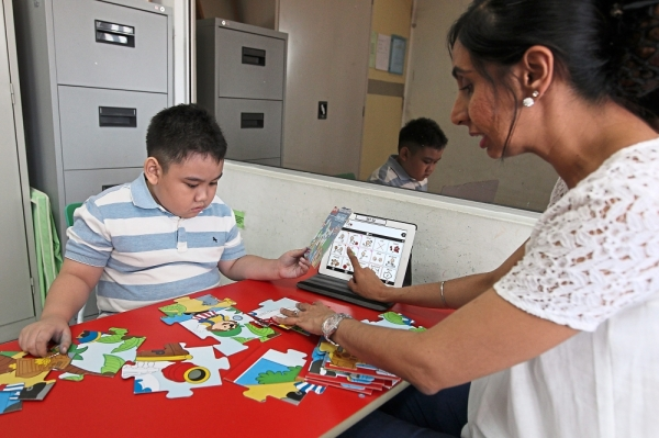 Dr Susheel uses apps during her therapy session to help her student develop speech. — GLENN GUAN/The Star