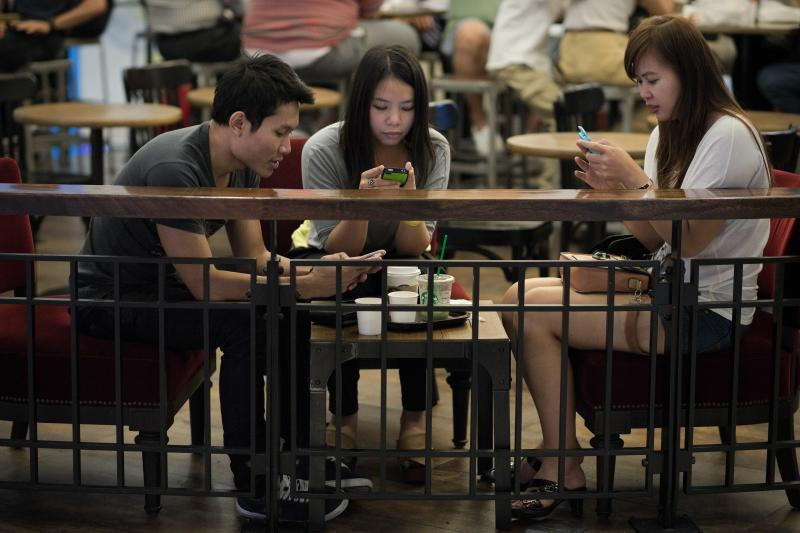 A file photo of shoppers looking at their smartphones at a coffee shop in a shopping mall in Bangkok. According to a university survey, post-coup, the consumer confidence index rose to 70.7 in May from 67.8 in April, after falling for 13 straight months - AFP Photo.
