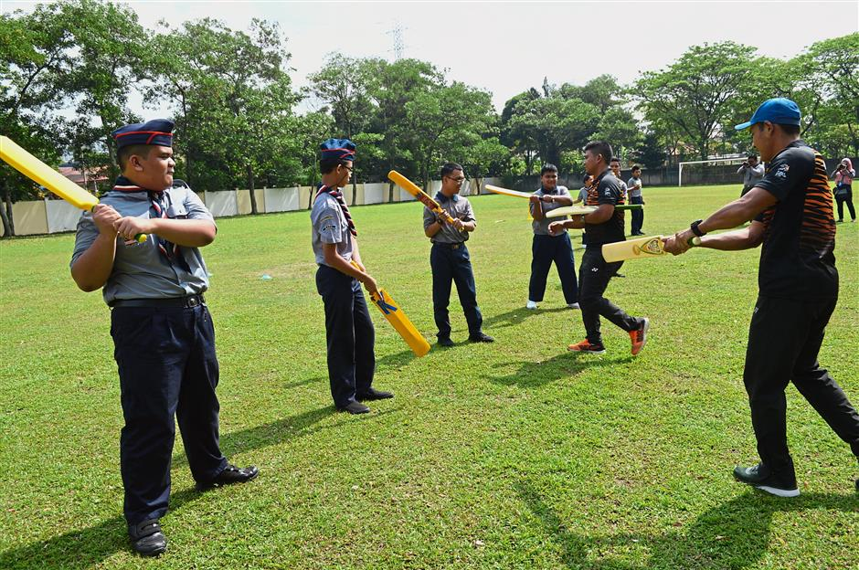 National cricket players Mohd Shukri Abdul Rahim (far right) and Mohd Shafiq Shariff (second from right) sharing some basic skills with students of SMK Batu Muda, Sentul.