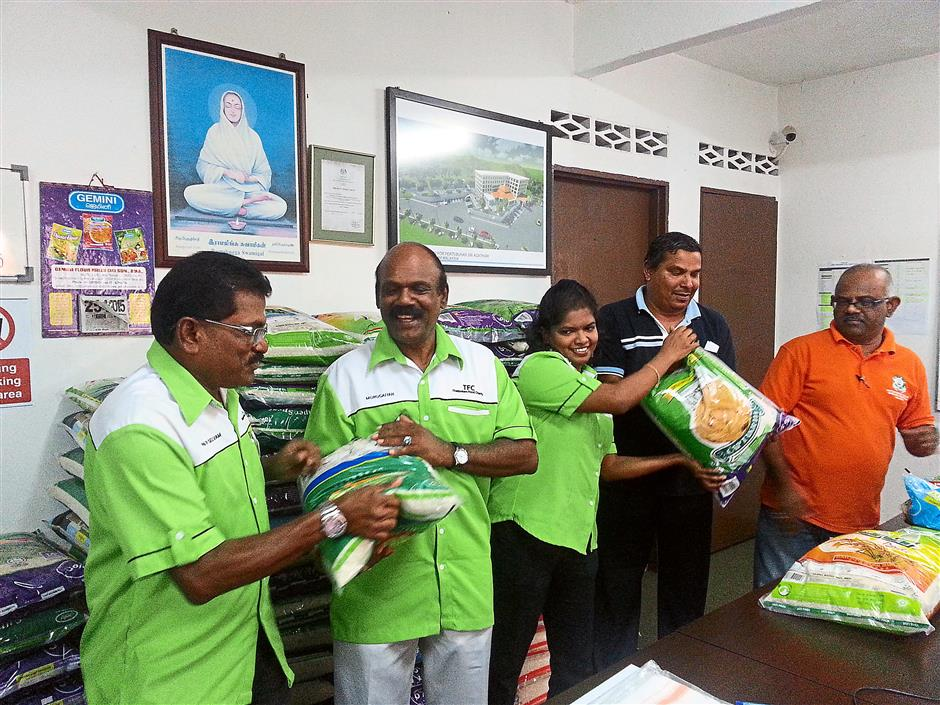 Grateful: Panirselvam (left) and his committee members arranging rice packets donated by members and the public for the upcoming Thaipusam Food Charity 2015.
