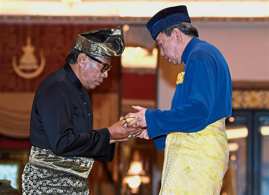 Sultan Sharafuddin presenting letter of appointment to