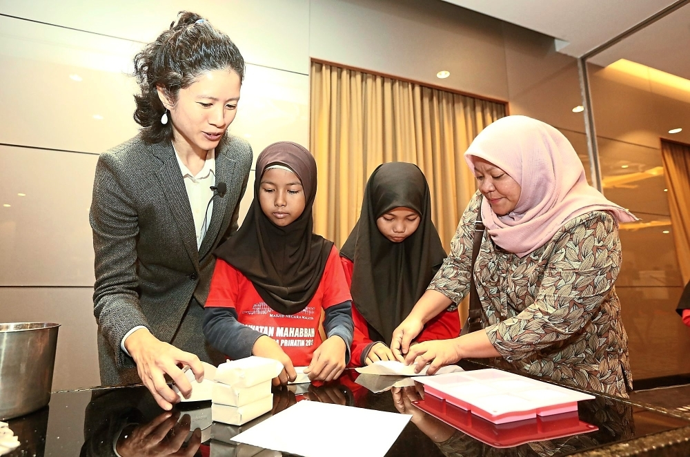 Kinder Soaps Sdn Bhd founder Michelle Ho (left) teaching Shahniza (second from left) and Norfaradyna (second from right) about soap packaging with help from the orphanage's secretary-general Makhfuzah Mohd Yusoff.