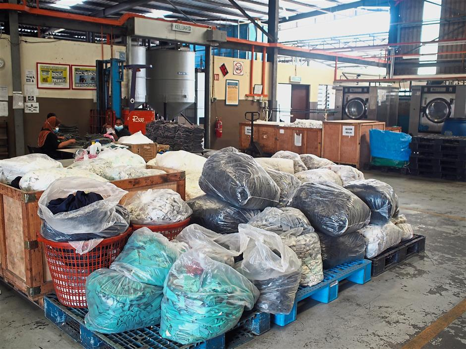 A look into the companys premises in Rembau, Negri Sembilan. In the background, some of the workers can be seen sorting through cloth and gloves that have been chemically treated.