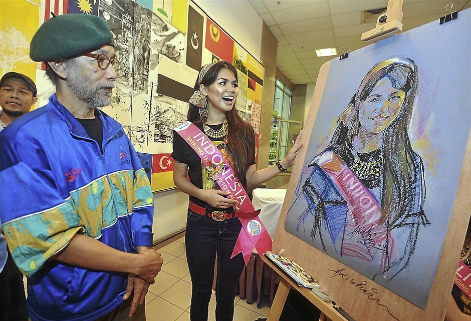 Happy with the result: Miss Tourism Indonesia Kalia Labitta Yudhasoka views her portrait drawn by artist Aris Aziz.