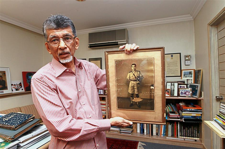 Hajeedar holding a portrait of his father Abdul Majid Ismail who was the liaison officer with the Reid Commission in 1956.