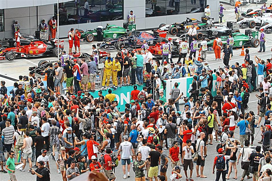 Crowds of spectators trying to get a closer look at the winners after the race at the prize giving ceremony for the 2014 Formula 1 Petronas Malaysia Grand Prix at Sepang International Circuit on March 30, 2014.