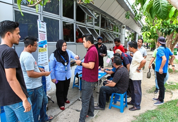 Nurul Asyikin (third from left) providing details on the self-employed social security scheme to e-hailing drivers during the campaign in Sepang.