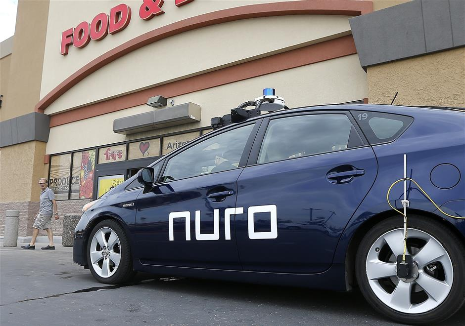 A self-driving Nuro vehicle parks outside a Fry\'s supermarket, which is owned by Kroger, as part of a pilot program for grocery deliveries Thursday, Aug. 16, 2018, in Scottsdale, Ariz. Kroger Co. has chosen the Phoenix suburb as a test market for delivering groceries using driverless cars. The Toyota Prius will be used for the deliveries, manned by a human to monitor its performance. During phase two in the fall, deliveries will be made by a completely autonomous vehicle, called an R1, with no human aboard. (AP Photo/Ross D. Franklin)