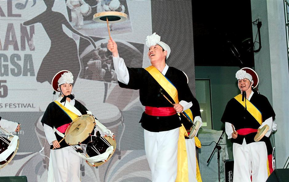 Balancing act: Performers from South Korea's Dongguk University performing a Pangut dance, a Korean folk music dance incorporating the use of streaming white ribbons on their hats and synchronising various parts of the body into fluid movements.