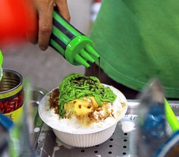 A worker preparing durian cendol. Other desserts like durian ice kacang, ice cream and smoothies are just as popular. (Right) Durian stalls are often packed with customers after working hours as some prefer to enjoy the fruit for dinner or have it as dessert.