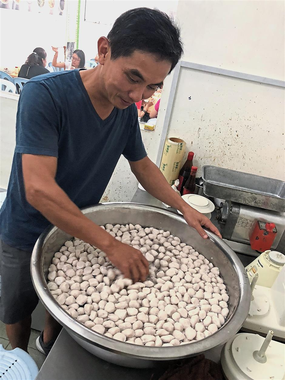 Lim (left) says he takes at least three to four hours to blend and hand-press the fish paste into fish balls and fish cakes every day as it is not an easy process.