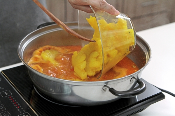After adding the pineapple stock, bring it to a boil. Then, add pineapple slices. — Photos: YAP CHEE HONG/The Star
