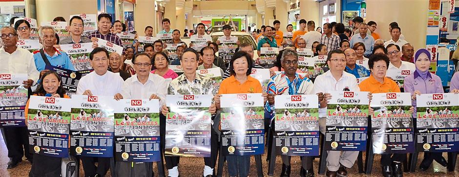 Say no to violence: Lau (from row fifth from left) with Dr Rais on her left and others holding the poster.