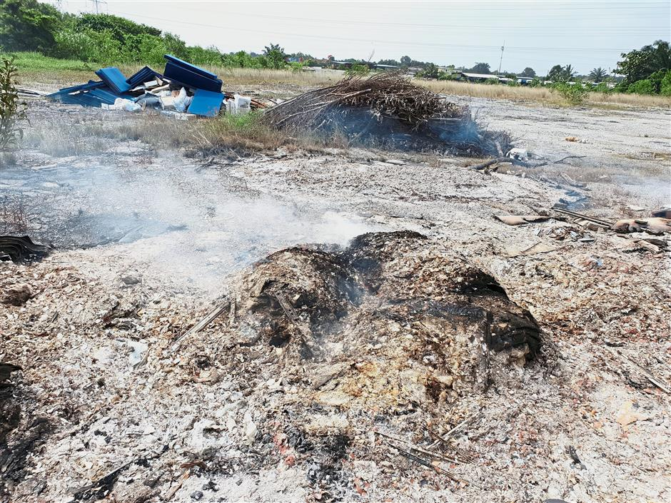 An illegal dumping spot with smouldering smoke due to open burning activities in Kampung Johan Setia.
