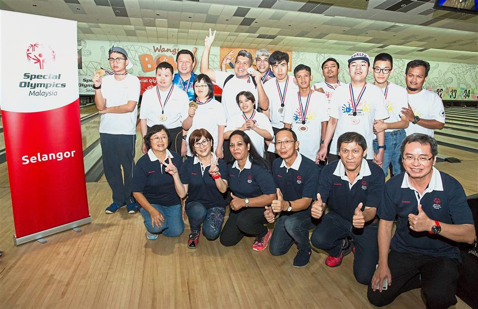 Top performers at the SOS Unified Bowling Tournament and SOS committee members (front row) after the event. — Photos: MUHAMAD SHAHRIL ROSLI/The Star and courtesy of Special Olympics Selangor