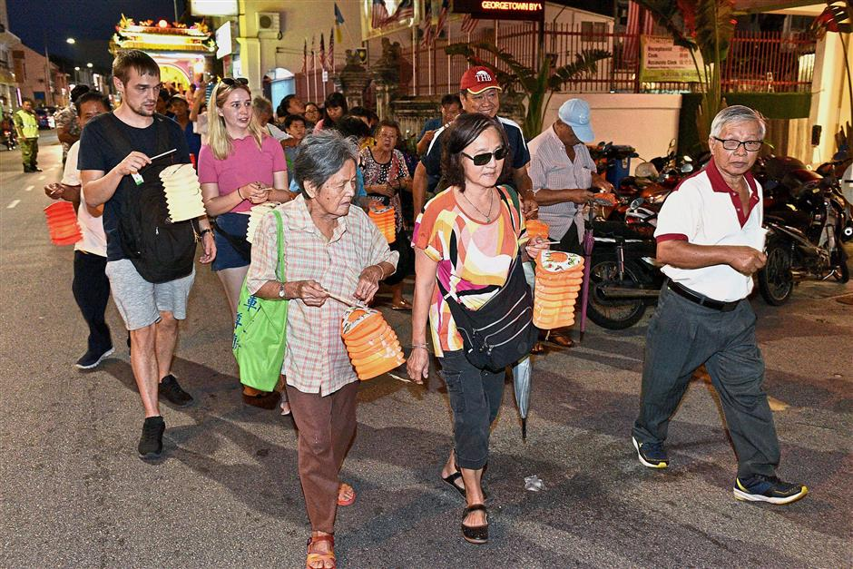 Locals and tourists joining the 1km walk along Chulia Street with traditional lanterns in hand.