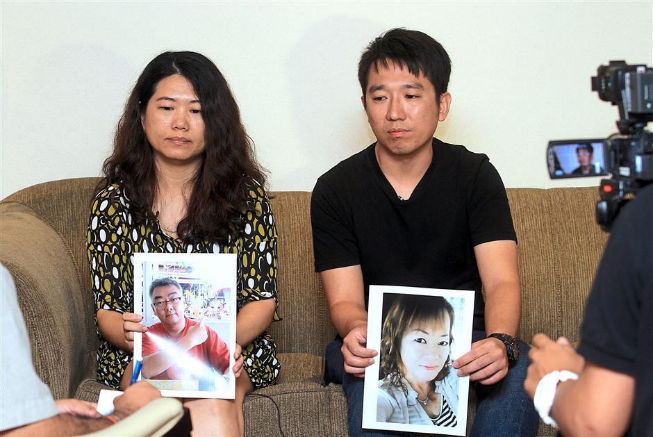 Desperate for contact: Chan (left) and Chung holding photos of their kidnapped loved ones.