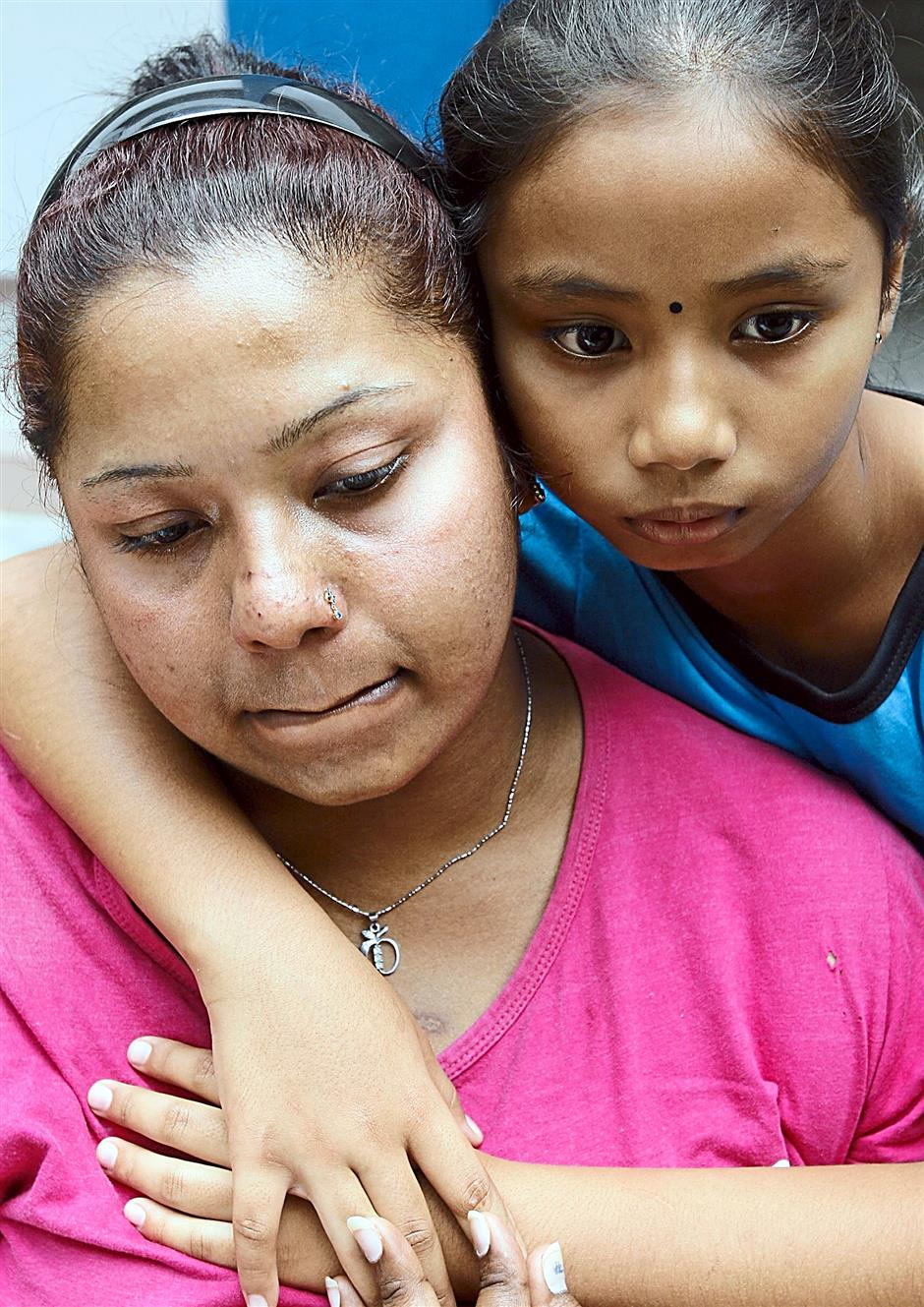 S.Deepa with her nine-year-old daughter V.Sharmila after lodging a report at the Seremban 2 police station. UU BAN/The Star