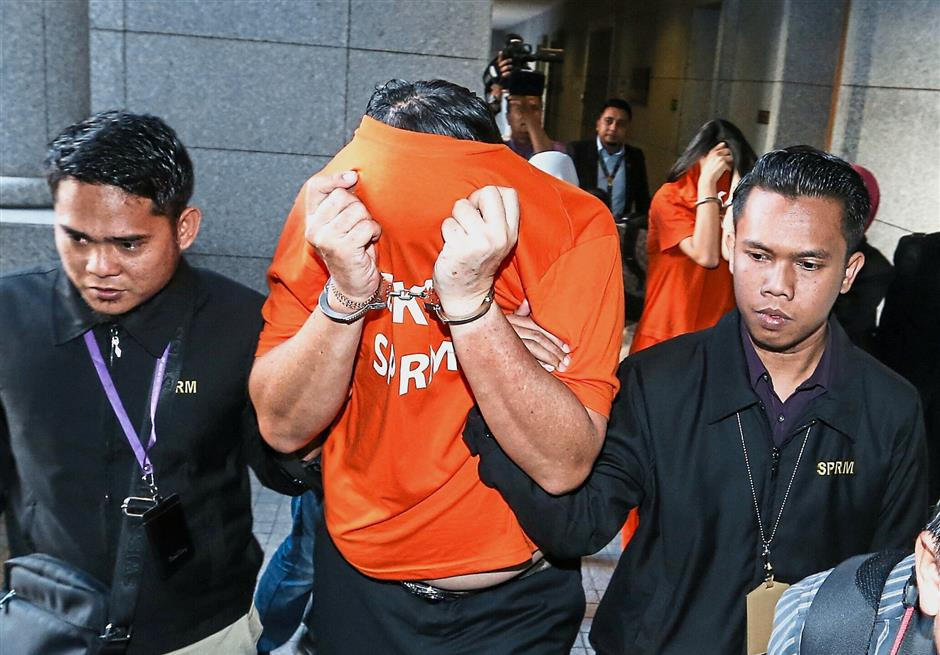 Walk of shame: Siew covering his face after being remanded at the magistrate's court in Putrajaya.