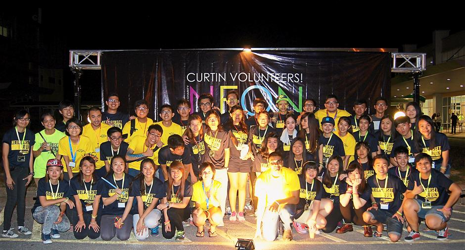 Students of Curtin University Sarawak posing for group photo during the Curtin Neon Sunset Run 2015. Pic by Ansovina Chai.