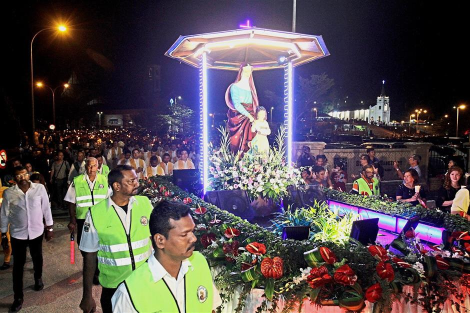 The float carrying the statues of St Anne and her daughter, the Blessed Virgin Mary, is taken on a 3km journey during the St Anne's Novena and Feast Day celebration. — Photos: CHAN BOON KAI/The Star