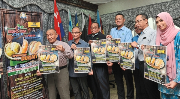 State Islamic Religious Affairs, Agriculture and Rural Development Committee chairman Tosrin Jarvanthi ( left), Johor Agriculture Department director Hishamuddin Ahmad (second from left) and staff showing the poster of state level agriculture expo and fruit fair 2019 in Segamat after the press conference at Johor Baru on June 19.