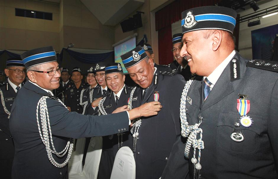 Well done: Mohamad Fuzi (left) having a light-hearted moment with Pingat Jasa Pahlawan Negara recipients at the Police Training Centre in Kuala Lumpur.