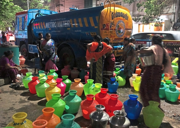 Daily struggle: Chennai's womenfolk lining up at night to collect water in 'kudams' or bright plastic pots.