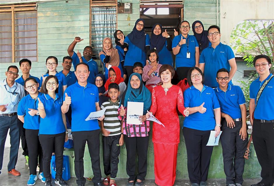 Hoo (front row, third from left), Tan (front row, fourth from right) and IJM Land Bhd employees with a recipient family.