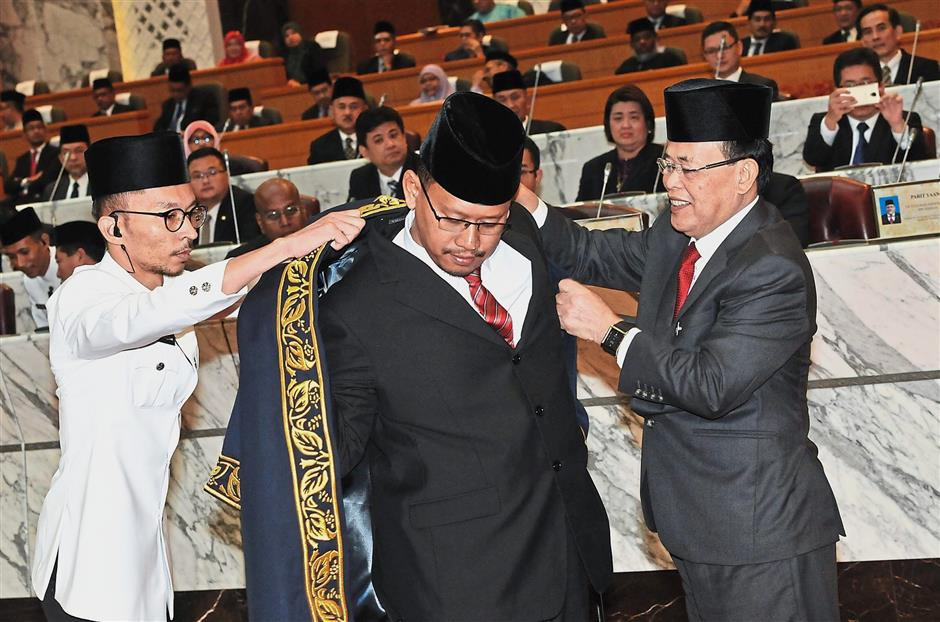 Johor Mentri Besar Datuk Osman Sapian (right) helping Suhaizan put on his robe after he was sworn in as Speaker.