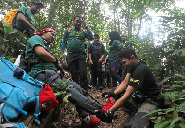 Hikers helping an injured teammate during the climb.