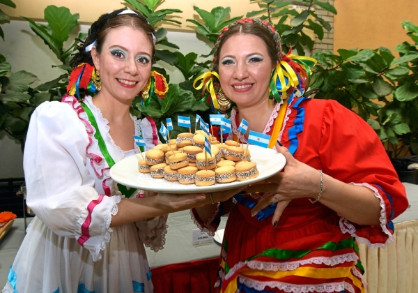 Performers of Mexican traditional folk dance, Janet Elizondo (left) and Janett Ontiveros with a common Argentinian sweet delicacy called alfajor.