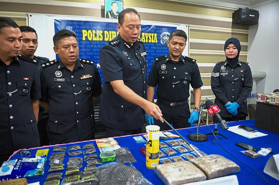 Student connection: Ahmad Dzaffir (centre) pointing out the seized drugs to the media in Kajang. — Bernama