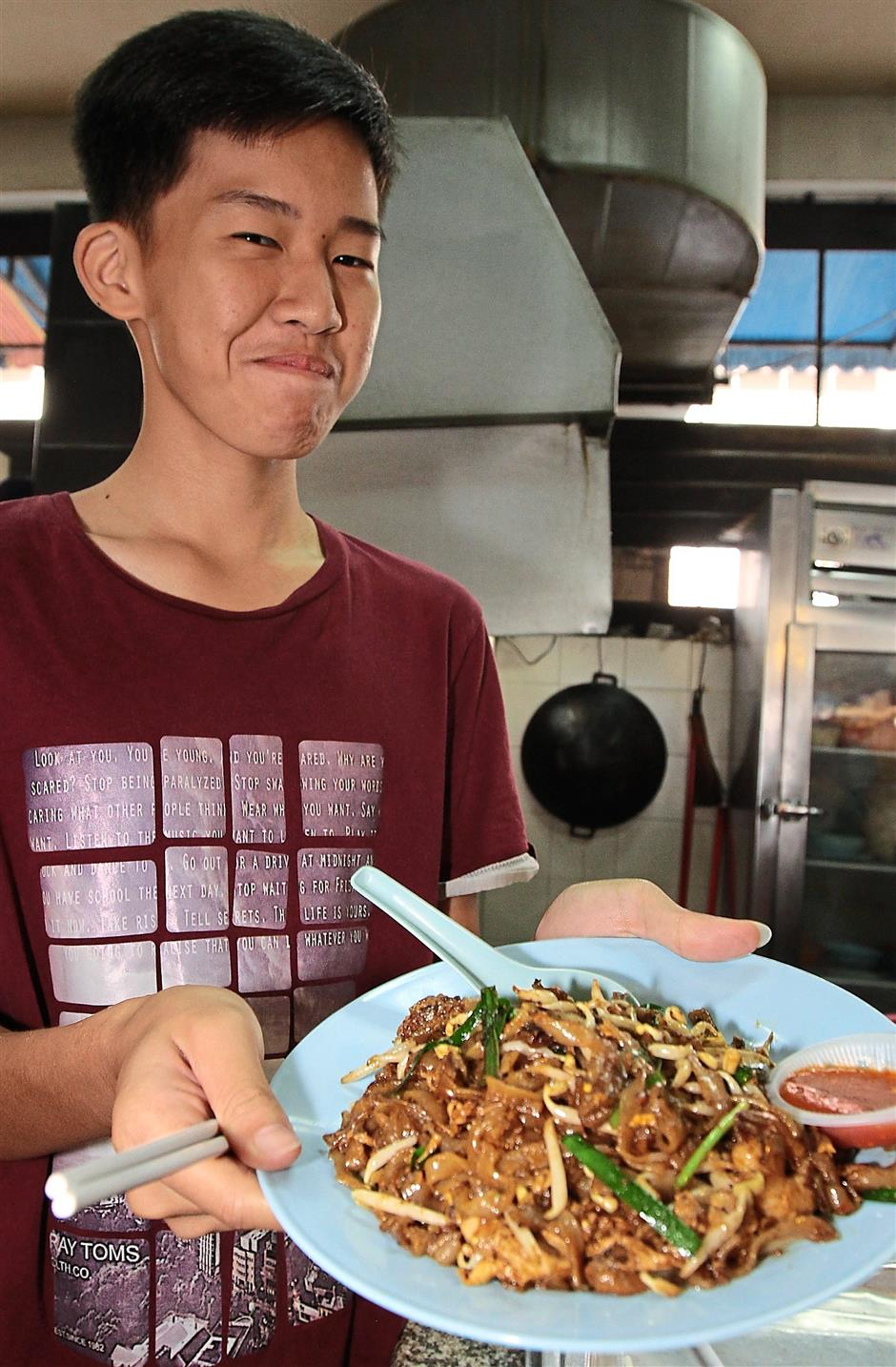 Benny Ng,14 holding up a char kuew teow that serve with cockles and prawn.Cockles were low in stocks due to Kuala Sepetang with high level of ammonia detected at the sea.