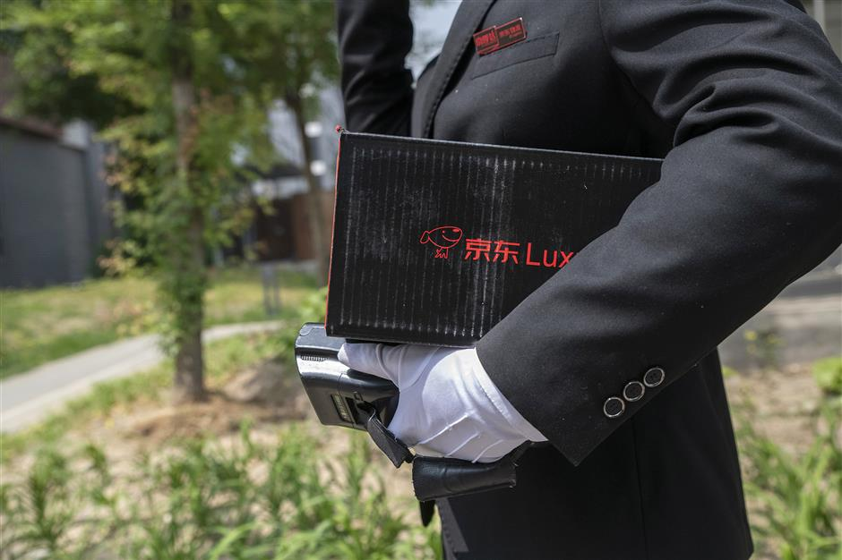 A driver for JD.com Inc.'s Luxury Express delivery service carries a customer's parcel in Beijing, China, on Thursday, May 16, 2019. Big names in luxury are teaming up with internet companies to offer sales and services like JD's white-gloved butler-style delivery that are rare in the U.S. Photographer: Gilles Sabrie/Bloomberg