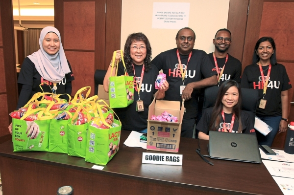 Terence (centre) and his team from the Group People Department preparing to distribute goodie bags to employees who gave feedback on improving the open day.(Below) A Star Media Group employee getting a free scoliosis screening at the Columbia Asia Hospital counter.