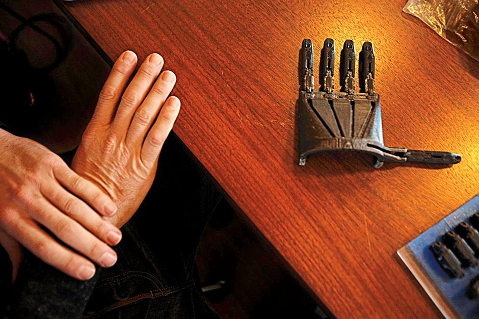 PLEASE USE IF POSSIBLE: A prosthetic hand created with 3D printing in the Not Impossible office, next to a real hand for scale and comparison.