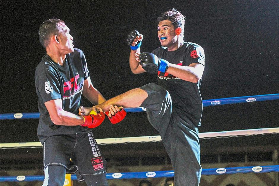 A fighter blocking a flying kick from his opponent in one of the matches.