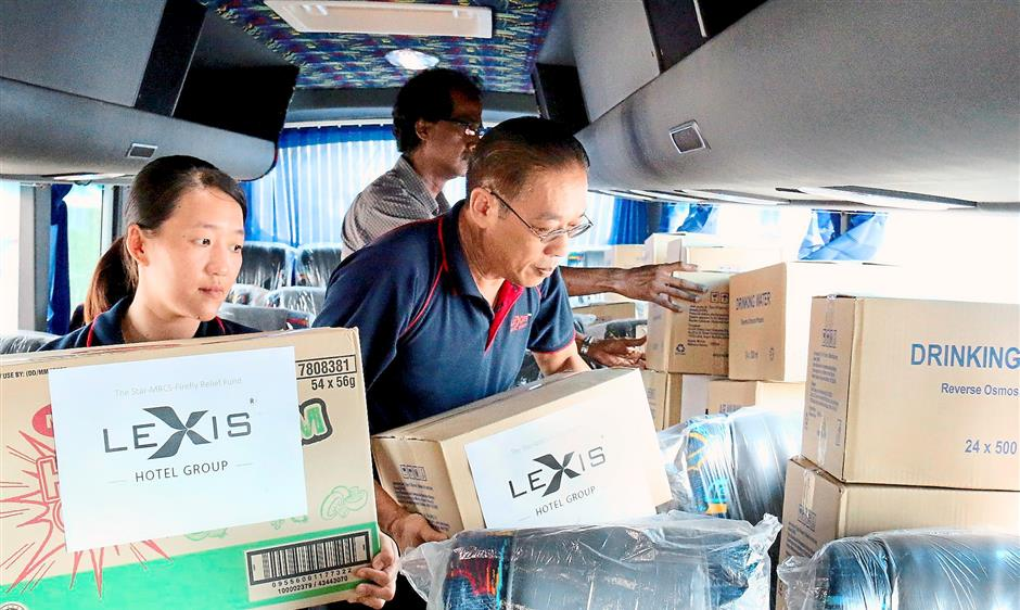 Trying to fit everything: Chan (right) and hotel employees arranging the boxes containing foodstuffs and drinking water in their own company bus.