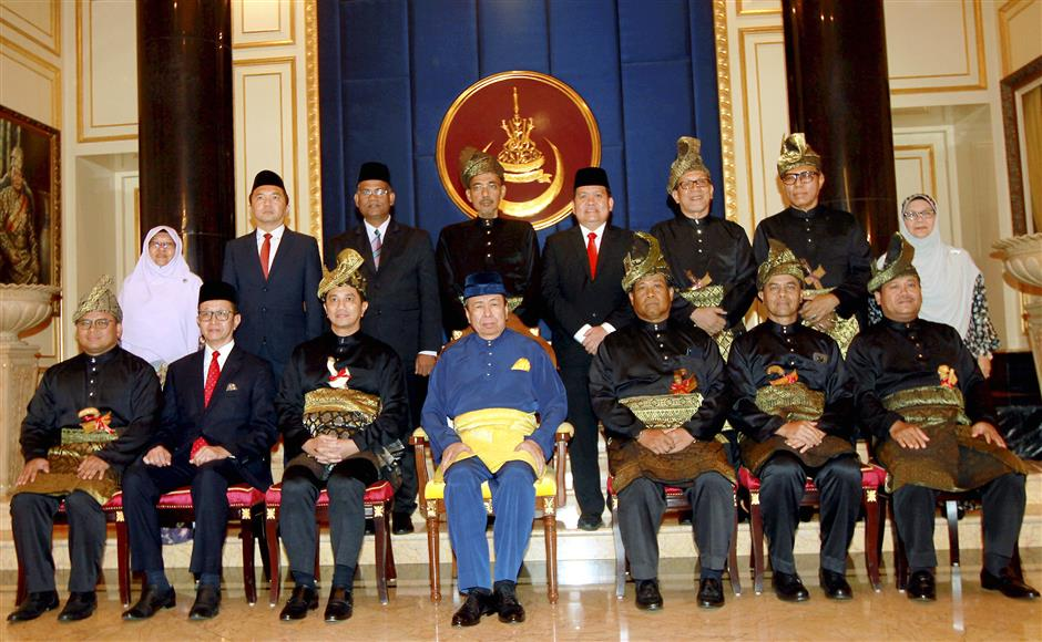 New team: Sultan Sharafuddin and Azmin (seated, third from left) with the new exco members in a group shot after the swearing-in ceremony at Istana Alam Shah in Klang.