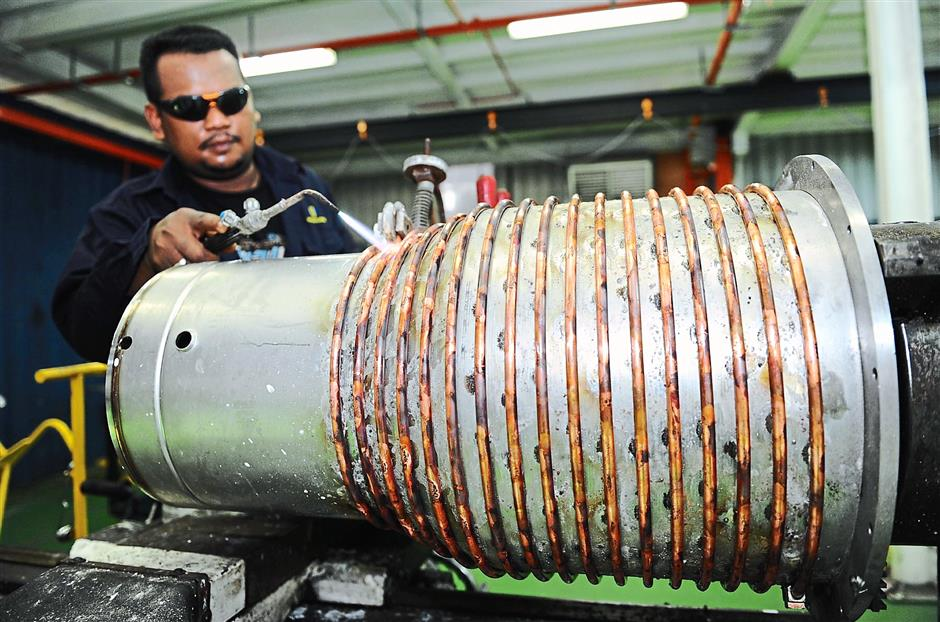 Top-selling product: Work being done on a diffusion pump at the company's production line in Bukit Minyak, Bukit Mertajam.